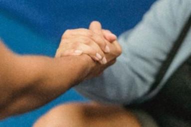 Un coach bien être qui tient la main à son patient pour l'aider